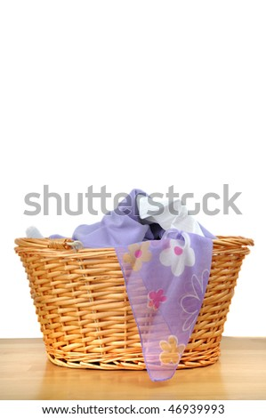 Lovely white and purple laundry in a wicker basket, isolated on white