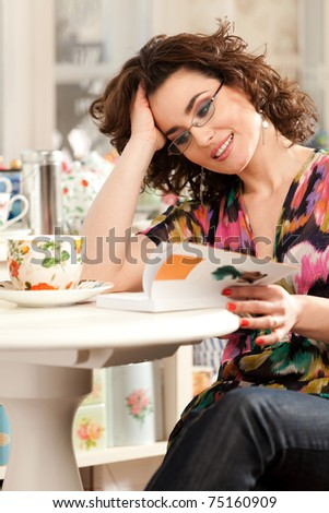 Lovely woman drinking her tea while is reading a book. See more images in the same shoot.