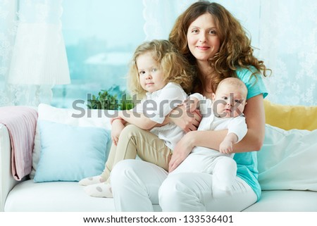 Lovely woman expressing her motherly love by hugging her babies - stock photo
