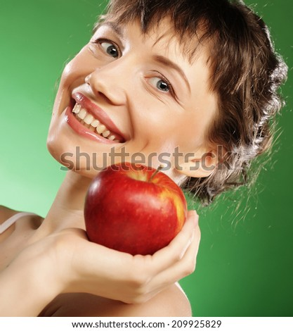 Lovely woman holding an apple next to her mouth. Over green background.