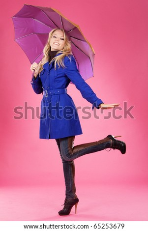 Lovely woman in a blue coat with umbrella against pink background
