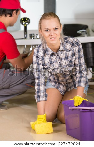 Lovely woman is cleaning the floor in the bathroom, while plumber repairs the pipes. - stock photo