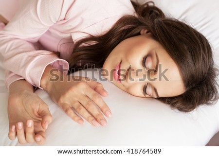 Lovely woman is sleeping on soft pillow