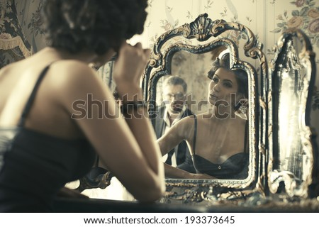 Lovely woman looking at mirror reflection.  - stock photo