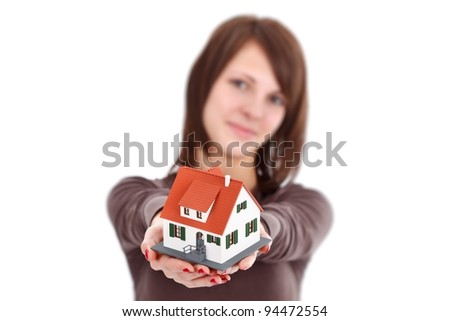 Lovely woman offering a miniature house, symbol of a new home - stock photo