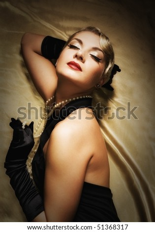 Lovely woman on golden fabric retro portrait - stock photo