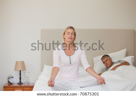 Lovely woman practicing yoga on her bed - stock photo