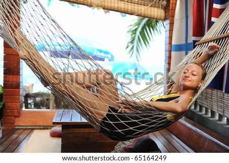Lovely woman relaxing in a hammock - stock photo