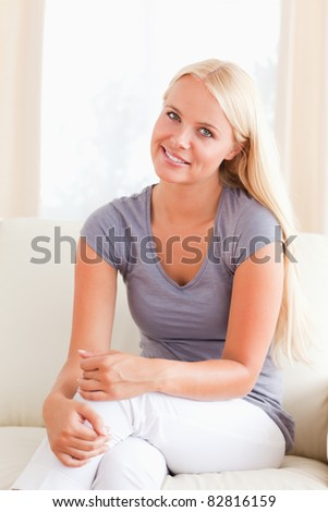 Lovely woman sitting on a sofa in her living room