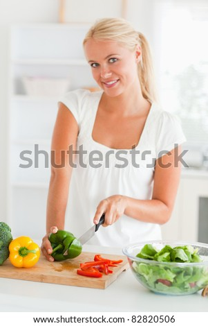 Lovely woman slicing pepper in her kitchen