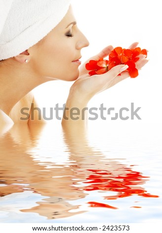 lovely woman smelling red flower petals in water - stock photo