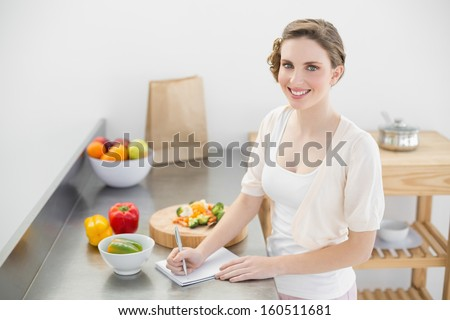 Lovely woman standing in her kitchen writing a shopping list smiling at camera