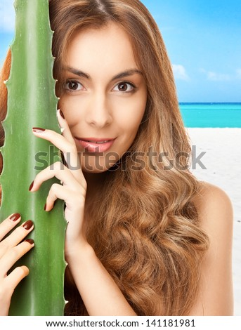 lovely woman with aloe vera over tropical beach background - stock photo