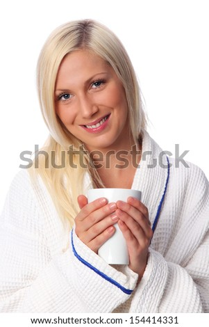 Lovely woman with blonde hair and blue Eyes, sitting down wearing a White bathrobe. White background.