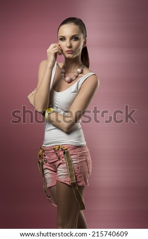 lovely woman with ponytail hair-style posing with casual clothes, suspenders and wrist watch  - stock photo