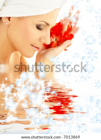 lovely woman with red flower petals and snowflakes in water - stock photo