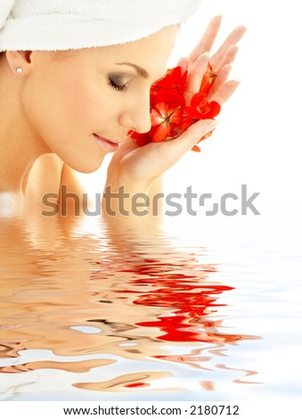 lovely woman with red flower petals in water - stock photo