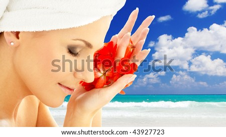 lovely woman with red flower petals over resort background - stock photo