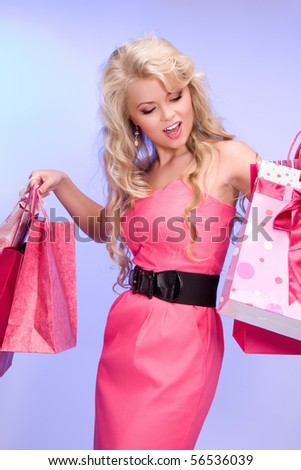 lovely woman with shopping bags over blue - stock photo