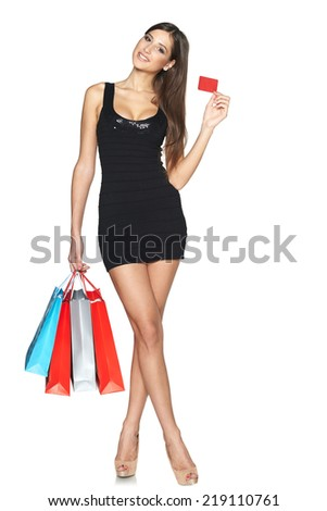 Lovely woman with shopping bags showing empty paper card, in full length over white background - stock photo