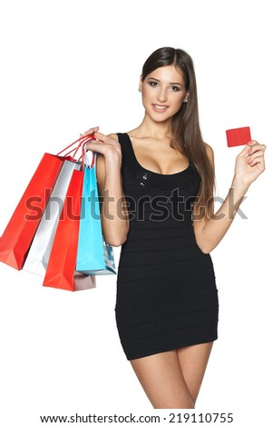 Lovely woman with shopping bags showing empty paper card, over white background - stock photo