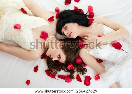 Lovely women posing in wedding dresses with petals - stock photo