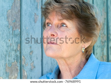 Lovely 70 year old woman looking up in thought with room or space for copy or text. - stock photo