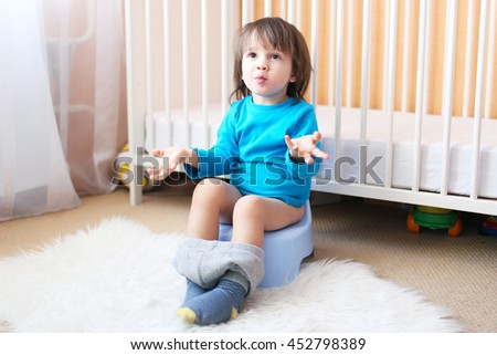 Lovely 2 years boy sitting on potty