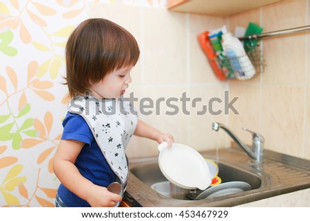 lovely 2 years little boy washing dishes