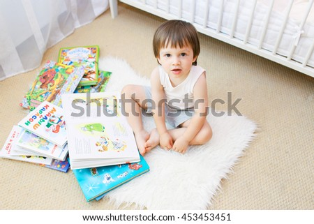 lovely 2 years toddler with books in his room