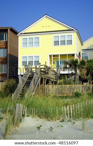 lovely yellow beach rental home - stock photo