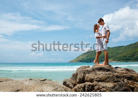 lovely young adult couple standing on the rocks above tropical sea - stock photo