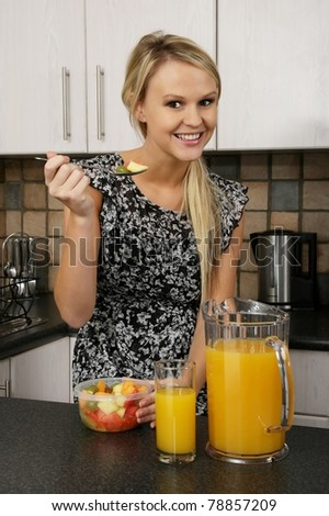 Lovely young blond woman enjoying a meal of healthy fruit and orange juice - stock photo