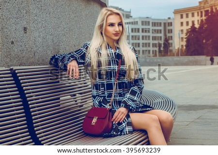 Lovely young blonde fashion model posing outdoors and looking away. fashion model posing outdoors. fashionable and glamour concept. - stock photo