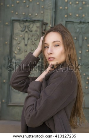 Lovely young  blonde woman in a grey coat at the street - stock photo