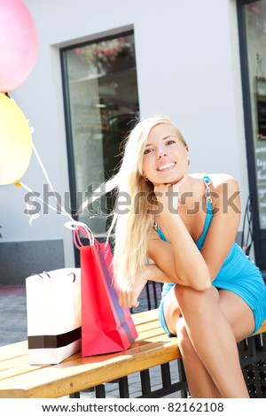 Lovely young blonde woman with shopping bags outdoors - stock photo