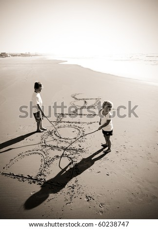 Lovely young brother and sister write words in the sand together - stock photo