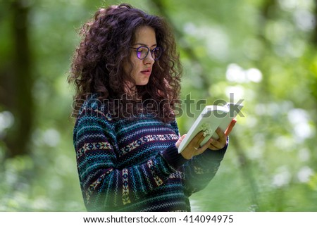 Lovely young brunette woman reading a book in a park, on a sunny day - stock photo