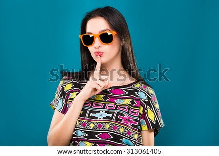 Lovely young brunette woman, wearing in colorful shirt and orange sunglasses, posing on the blue background, in studio, waist up - stock photo