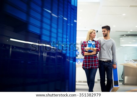 Lovely young couple are at shopping center. He is lugging big unpacked TV box, she is hugging gift. They are looking each other and walking towards camera. Shallow depth of field. - stock photo