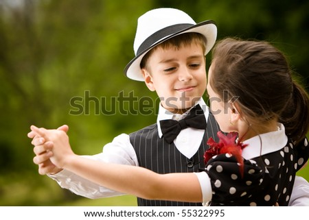 Lovely young couple dancing and having fun. Focus on the boy face. More images with the same models. - stock photo