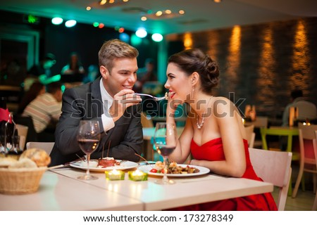 Lovely young couple eating on romantic dinner - stock photo