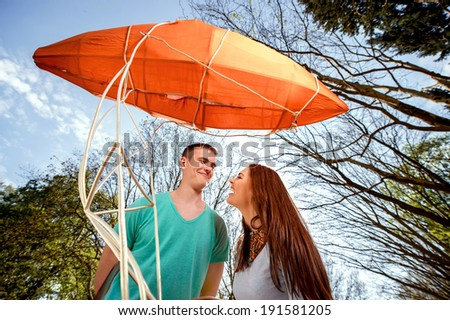 Lovely young couple flirting near the red dirigible in the park - stock photo