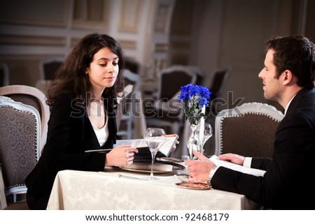 Lovely young couple having dinner in a romantic restaurant. Focus on the woman's face. Please see more images from the same shoot. - stock photo