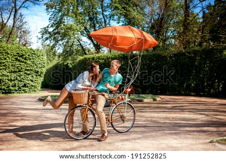Lovely young couple having fun with the bicycle with red dirigible in the park in the summer - stock photo