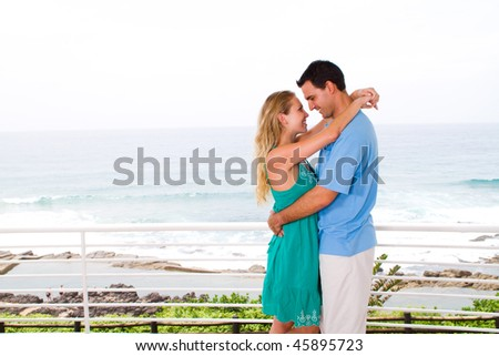 lovely young couple hugging, background is beautiful sea view