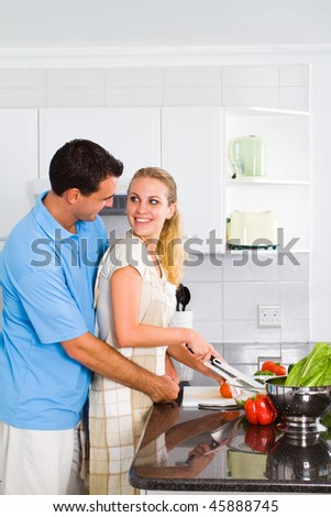lovely young couple in home kitchen preparing food