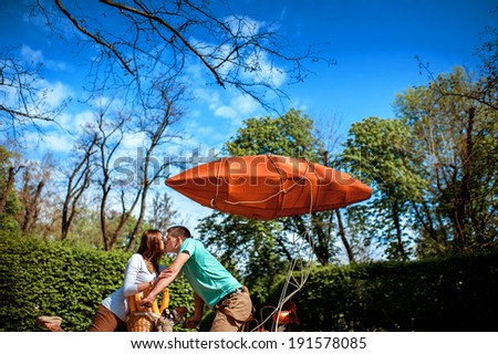 Lovely young couple kissing on the bicycle with red dirigible in the park in the summer - stock photo