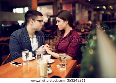 Lovely young couple looking at each other at cafe in trade center. Copy space for your text. Shallow depth of field. Very useful photo for processing with one click on edit image.