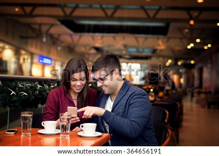 Lovely young couple looking at smart phone at cafe in trade center. Copy space for your text. Shallow depth of field. Very useful photo for processing with one click on edit image. - stock photo